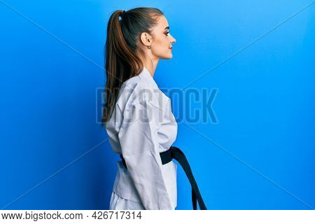 Beautiful brunette young woman wearing karate fighter uniform with black belt looking to side, relax profile pose with natural face with confident smile.