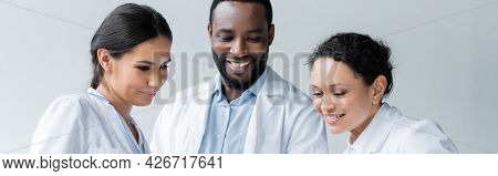 Smiling Interracial Doctors Looking Down In Clinic, Banner