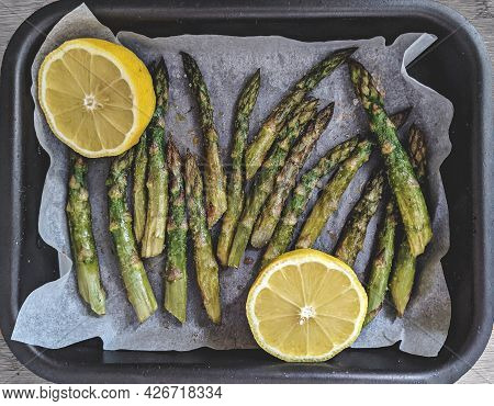 Baked Asparagus In Baking Dish Cooking In Oven And Half Of Lemon On Wooden Surface Table, Healthy Ea
