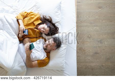 Top View Of Living Couple Lying In Bed With Smartphones.