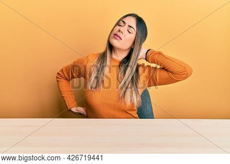 Young hispanic woman wearing casual clothes sitting on the table suffering of neck ache injury, touching neck with hand, muscular pain