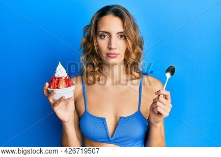 Young caucasian woman wearing bikini eating ice cream relaxed with serious expression on face. simple and natural looking at the camera.