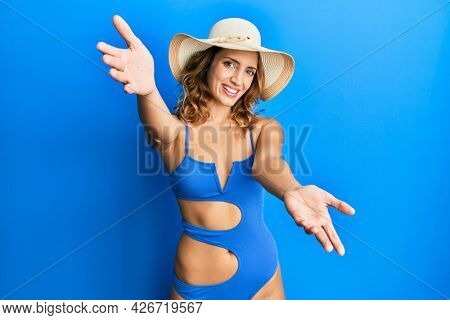 Young caucasian woman wearing bikini and summer hat looking at the camera smiling with open arms for hug. cheerful expression embracing happiness.