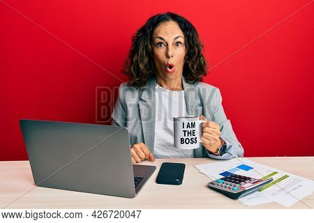 Beautiful middle age woman drinking from i am the boss coffee cup scared and amazed with open mouth for surprise, disbelief face