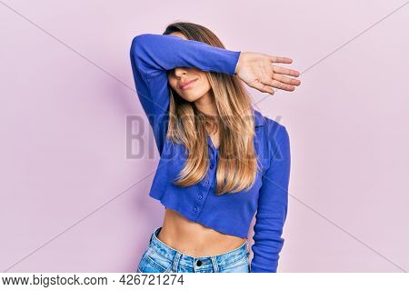 Beautiful hispanic woman wearing casual blue shirt covering eyes with arm, looking serious and sad. sightless, hiding and rejection concept