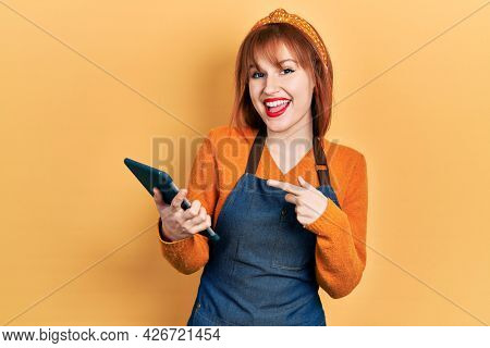Redhead young woman wearing waitress apron holding touchpad device taking order smiling happy pointing with hand and finger