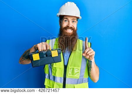 Redhead man with long beard wearing safety helmet and reflective jacket holding toolbox smiling with an idea or question pointing finger with happy face, number one