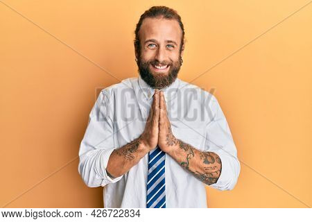 Handsome man with beard and long hair wearing business clothes praying with hands together asking for forgiveness smiling confident.