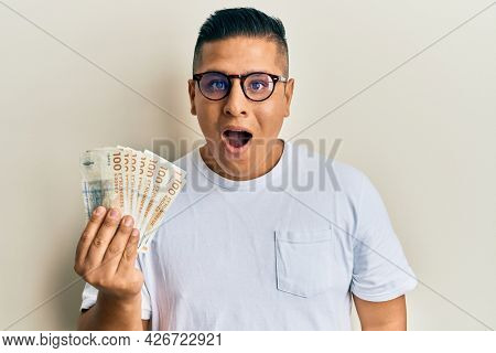 Young latin man holding 100 danish krone banknotes scared and amazed with open mouth for surprise, disbelief face