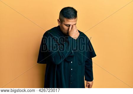 Young latin priest man standing over yellow background tired rubbing nose and eyes feeling fatigue and headache. stress and frustration concept.