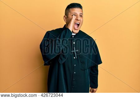 Young latin priest man standing over yellow background shouting and screaming loud to side with hand on mouth. communication concept.