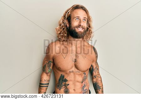 Handsome man with beard and long hair standing shirtless showing tattoos looking away to side with smile on face, natural expression. laughing confident.