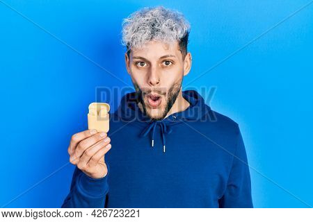 Young hispanic man with modern dyed hair holding wireless earphones scared and amazed with open mouth for surprise, disbelief face