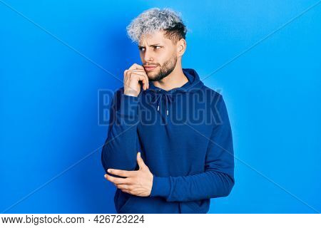 Young hispanic man with modern dyed hair wearing casual blue sweatshirt thinking concentrated about doubt with finger on chin and looking up wondering