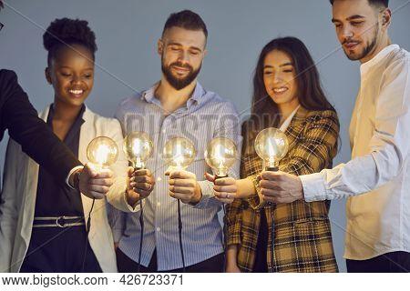 Diverse Multinational Group Of People Hold Lightbulb Together Studio Shot