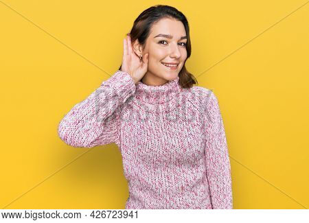 Young caucasian girl wearing wool winter sweater smiling with hand over ear listening an hearing to rumor or gossip. deafness concept.