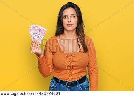 Beautiful hispanic woman holding 50 turkish lira banknotes thinking attitude and sober expression looking self confident