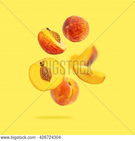 Flying Fresh Ripe Juicy Peaches Isolated On Yellow Background. Whole And Halved Peaches With Pits, S