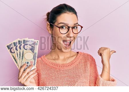 Young caucasian woman holding japanese yen banknotes pointing thumb up to the side smiling happy with open mouth