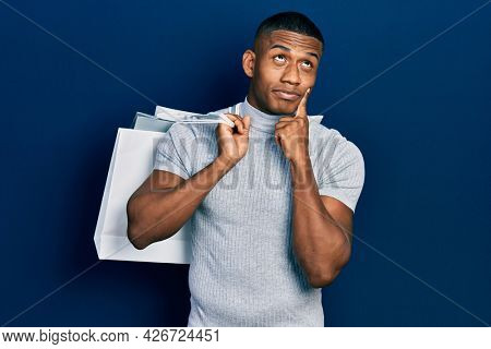 Young black man holding shopping bags serious face thinking about question with hand on chin, thoughtful about confusing idea