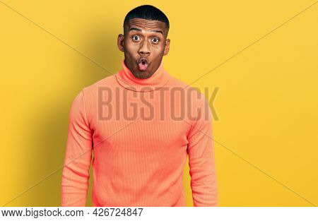 Young black man wearing orange turtleneck sweater scared and amazed with open mouth for surprise, disbelief face