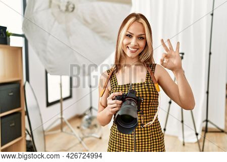 Young caucasian photographer girl holding professional camera at photography studio doing ok sign with fingers, smiling friendly gesturing excellent symbol