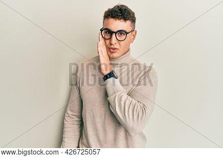 Hispanic young man wearing casual turtleneck sweater hand on mouth telling secret rumor, whispering malicious talk conversation