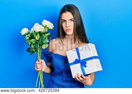 Young brunette teenager holding anniversary present and bouquet of flowers relaxed with serious expression on face. simple and natural looking at the camera.