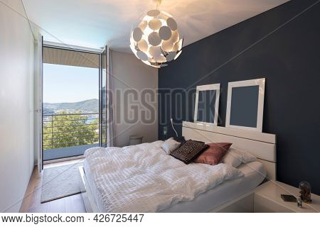 Elegant bedroom with large white bed and a balcony with a view of the valley with the lake. Nobody inside.