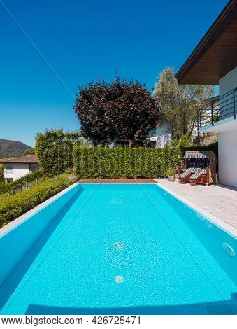 Front view pool with clear water and large green hedge, perfect for a vacation. Sunny day with blue skies and nobody inside.