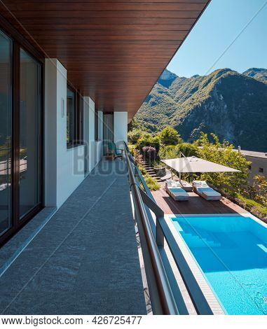 Balcony of villa with rock floor and wooden ceiling. Downstairs you can see the pool perfect for a swim. View of the green mountains of Switzerland. Nobody inside
