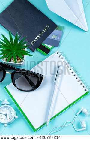 Vacation Planning. Travel Accessories On A Blue Background. Passport, Sun Glasses And Notepad. Flatl