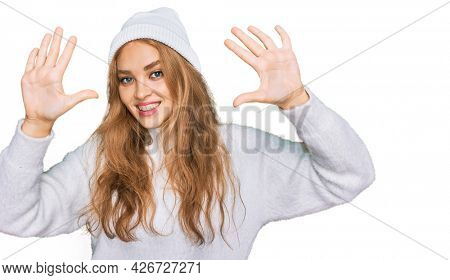 Young caucasian girl wearing wool sweater and winter cap showing and pointing up with fingers number ten while smiling confident and happy.