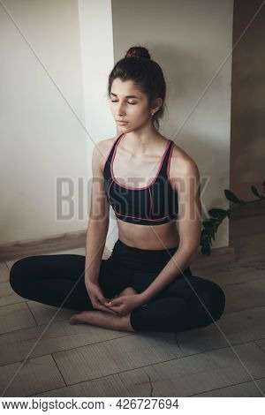 Brunette Woman Is Wearing Sportwear While Meditating On The Floor During A Fitness Session