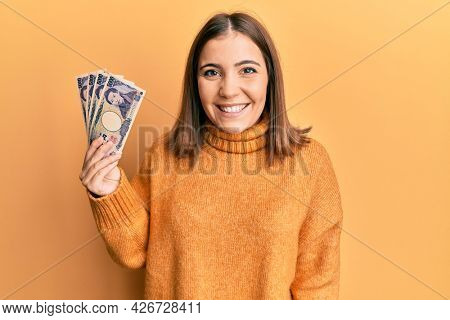 Young woman holding 5000 japanese yen banknotes looking positive and happy standing and smiling with a confident smile showing teeth