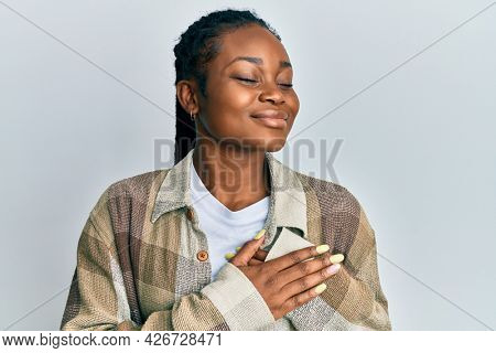 Young african american woman wearing casual clothes smiling with hands on chest, eyes closed with grateful gesture on face. health concept.