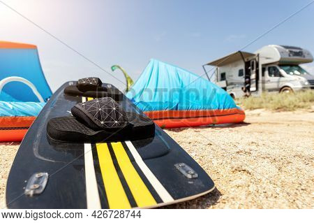 Close-up Surf Board And Kite Equipment On Sand Beach Shore Watersport Spot On Bright Sunny Day Again
