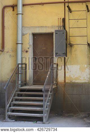 Entrance To The Building With A Metal Door And A Metal Staircase With A Porch