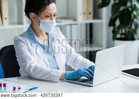 African American Scientist In Medial Mask Using Laptop Near Digital Tablet And Blurred Test Tubes