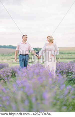 Mature Couple In Love Holding Hands In The Lavender Field. Happy Middle Aged Couple Walking Outside