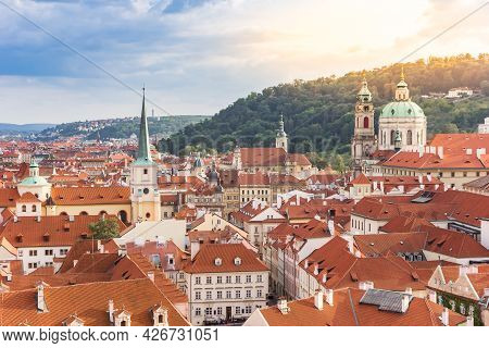 Evening Sun Over Church Towers And Rooftops In Prague, Czech Republic