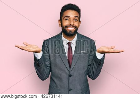 Young african american man wearing business clothes clueless and confused expression with arms and hands raised. doubt concept.