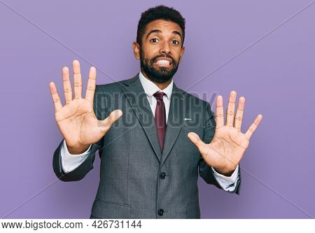 Young african american man wearing business clothes afraid and terrified with fear expression stop gesture with hands, shouting in shock. panic concept.