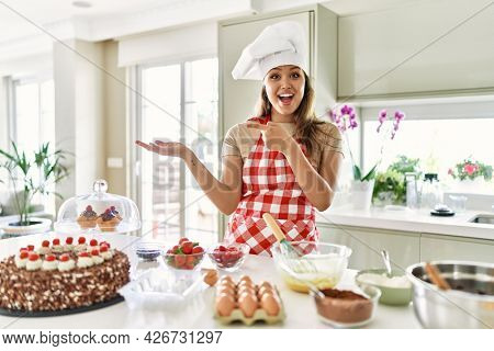 Beautiful young brunette pastry chef woman cooking pastries at the kitchen amazed and smiling to the camera while presenting with hand and pointing with finger.