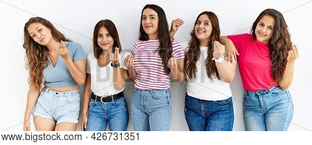Group of women wearing casual clothes standing over isolated background doing money gesture with hands, asking for salary payment, millionaire business
