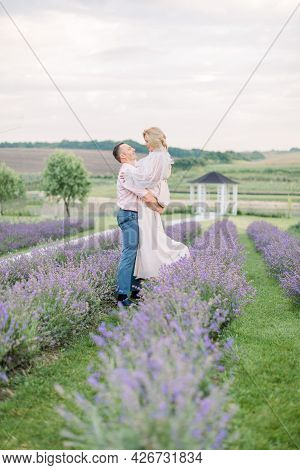 Happy Middle Aged Lovely Couple In Purple Lavender Flower Field, Have Romantic Time And Wedding Anni