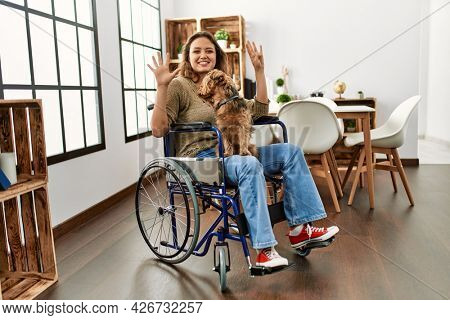 Young hispanic girl sitting on wheelchair at home showing and pointing up with fingers number ten while smiling confident and happy.