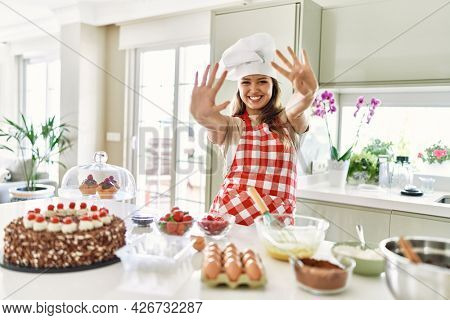 Beautiful young brunette pastry chef woman cooking pastries at the kitchen showing and pointing up with fingers number nine while smiling confident and happy.