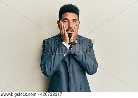 Handsome hispanic man with beard wearing business suit and tie tired hands covering face, depression and sadness, upset and irritated for problem