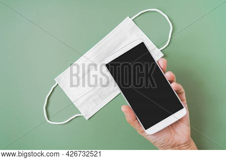 Hand Holding White Smart Phone With Clipping Path On Touchscreen On Face Mask On Green Background Fo